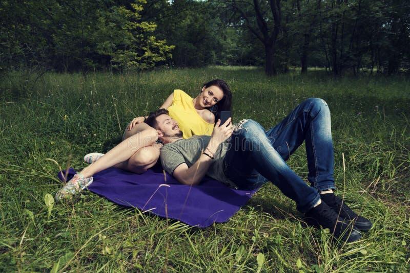 放下在紫色毯子和听的音乐的年轻夫妇在智能手机 库存照片