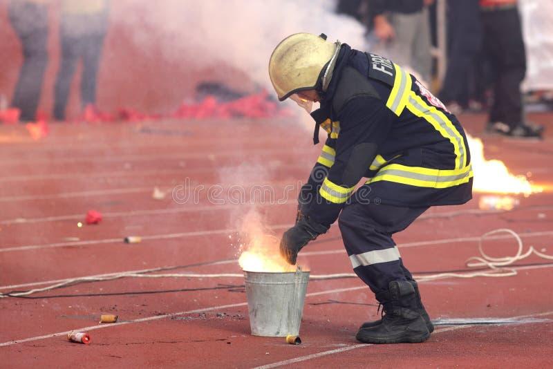 放下足球迷的火炬火的消防队员 库存照片
