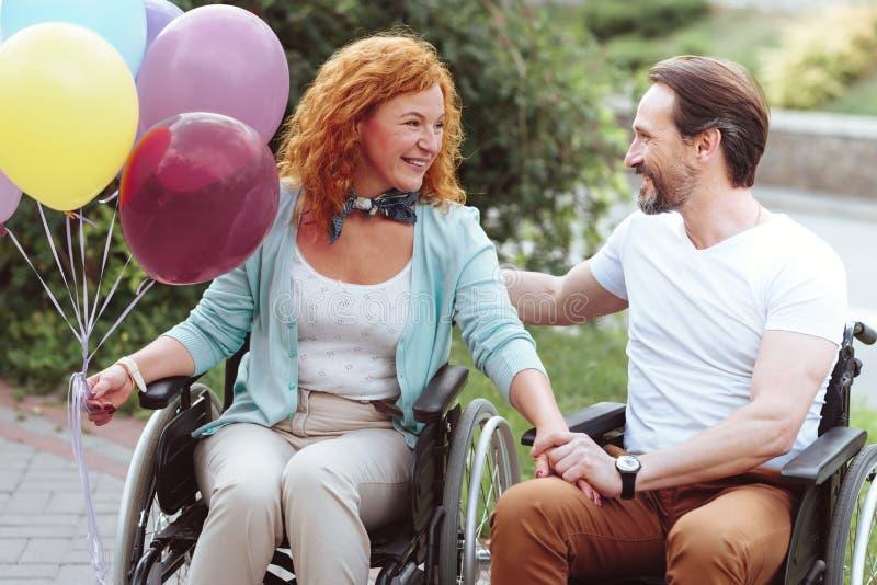 放光光芒四射的残疾的夫妇聊天和户外 免版税图库摄影