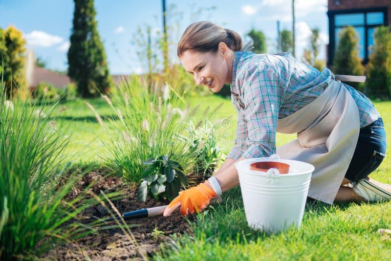 放光的花匠在她的手上的拿着一点锄,当除草根除草时 图库摄影
