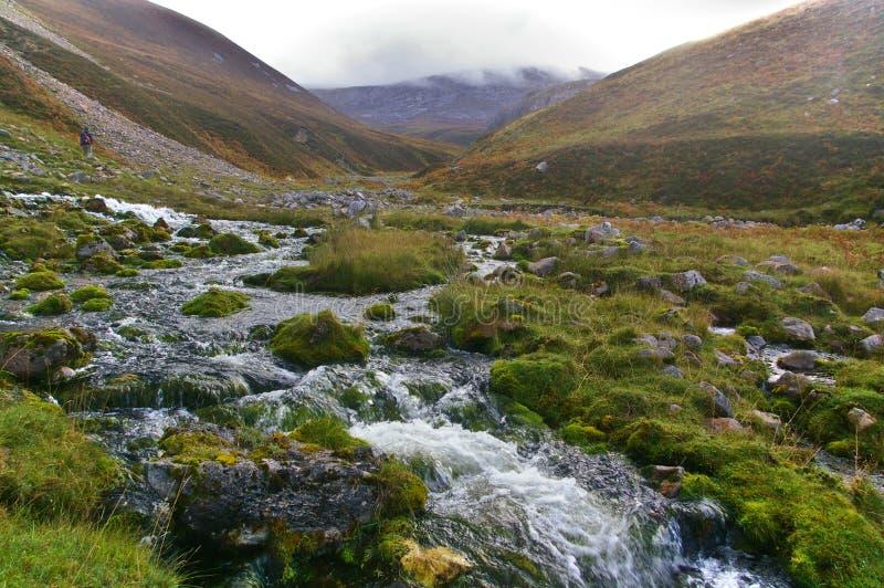 放出在山的一个岩石谷与远足者 免版税库存图片