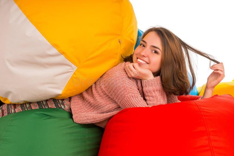 放在装豆子小布袋椅子之间的年轻愉快的妇女 免版税图库摄影