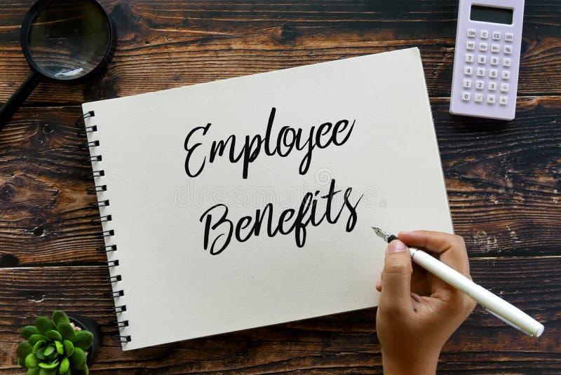 放大镜、植物、计算器和手写雇员福利的候宰栏顶视图在木背景的笔记本 免版税库存照片