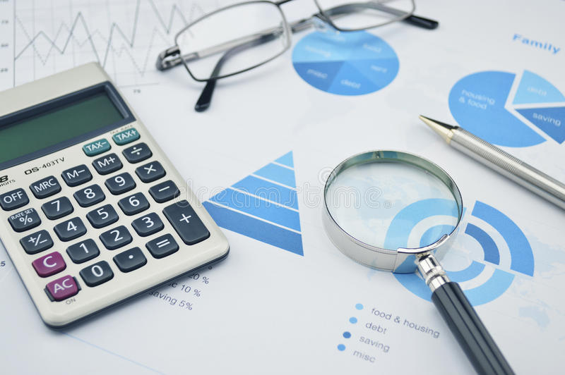 放大镜、笔、玻璃和计算器在家庭预算g 库存图片