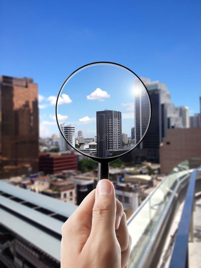 放大镜和都市风景在焦点 库存图片