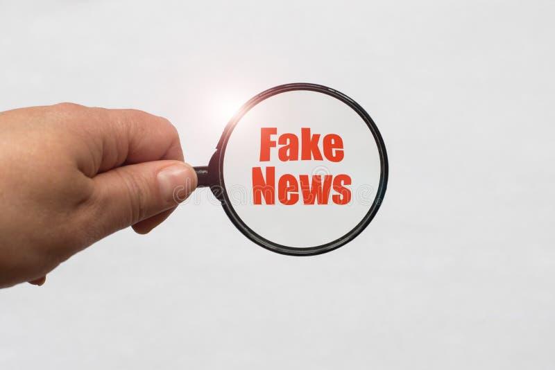 放大镜在手中和在白色背景的一个假新闻词 库存图片