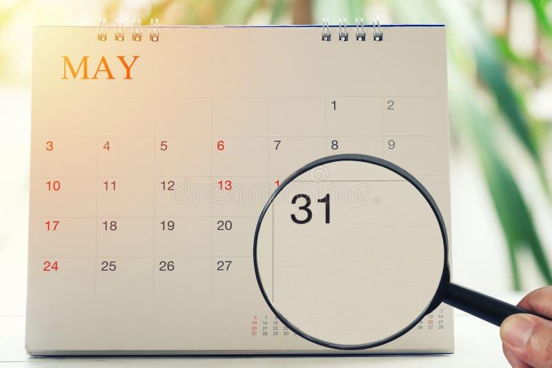 放大镜在日历您能在手中看三十一天 免版税库存图片