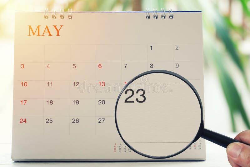 放大镜在日历您能在手中看二十三个d 免版税图库摄影