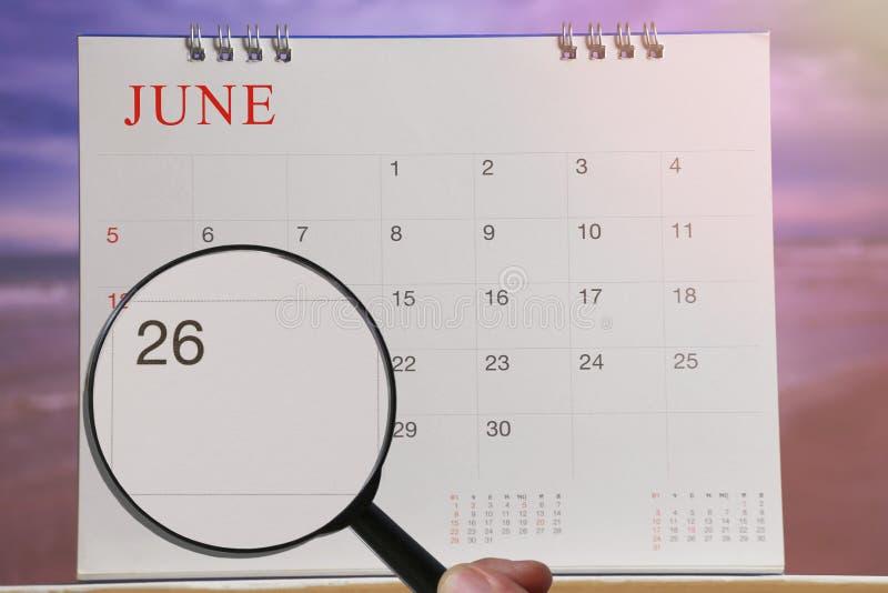 放大镜在日历您能在手中看二十六天 库存照片