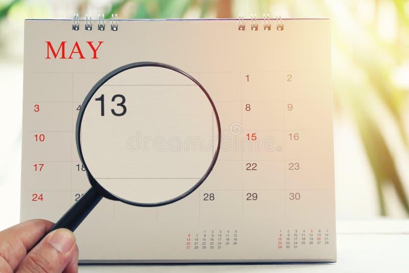放大镜在日历您能在手中看十三天o 免版税库存照片