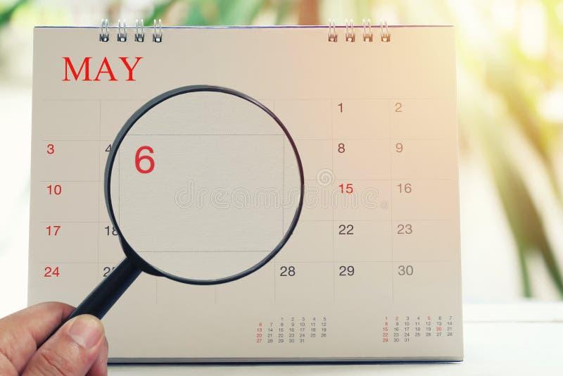 放大镜在日历您能在手中看第六天m 库存照片