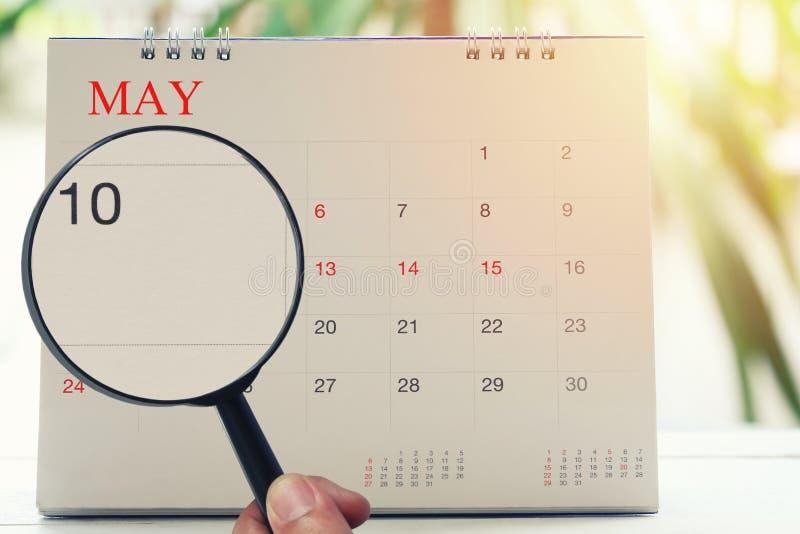放大镜在日历您能在手中看第十天m 免版税库存照片
