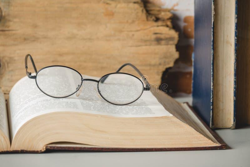 放大镜特写镜头与开放书的在桌上 免版税库存照片