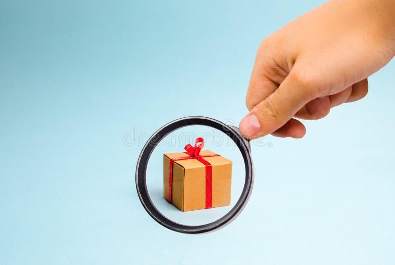 放大镜看在蓝色背景的礼物盒 简单派 新年假日或生日的方法 免版税库存照片