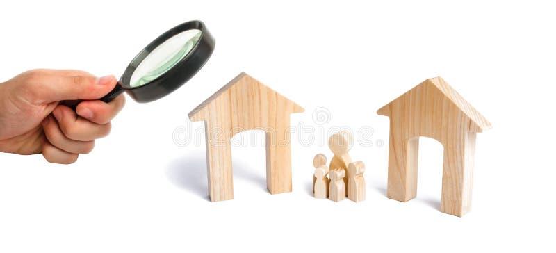放大镜看有孩子的家庭站立在两个房子之间 未来家庭的指定 免版税库存图片