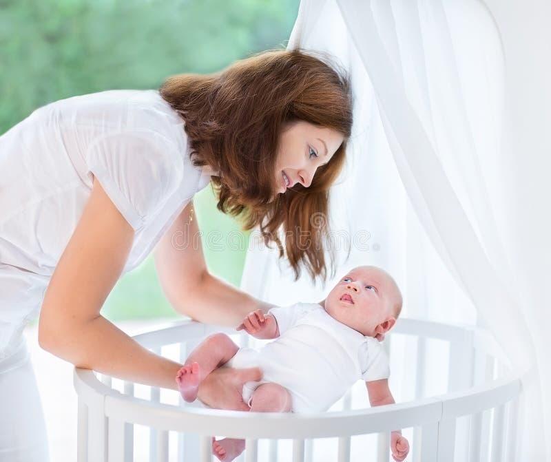 放她新出生的婴孩的年轻母亲入小儿床 免版税图库摄影