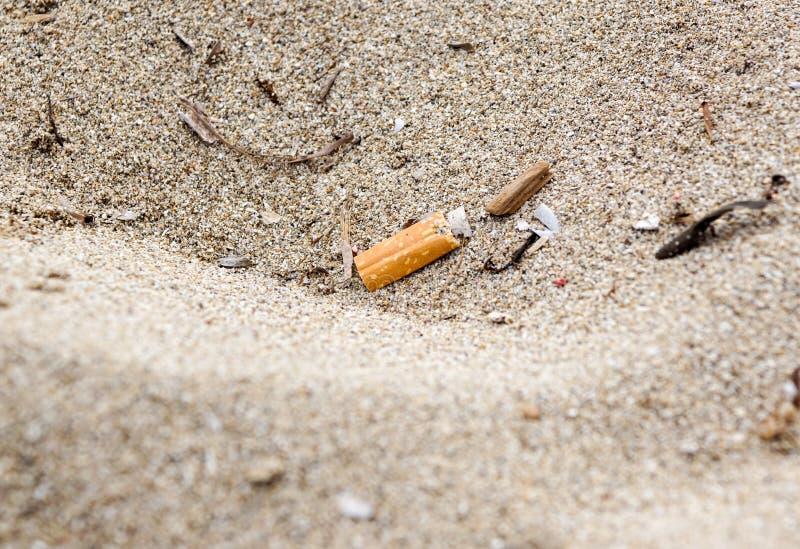 放弃在海滩的烟头,沙子不是好,软的焦点,被弄脏 免版税库存图片