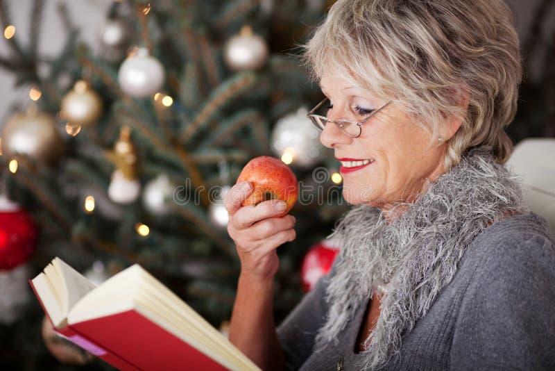 放松与书和苹果的资深夫人 免版税图库摄影