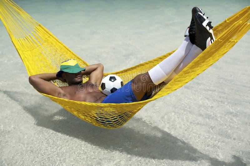 放松与在海滩吊床的橄榄球的巴西足球运动员 免版税库存图片