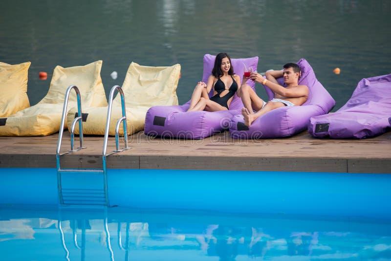 放松与在被缓冲的懒人的背景的饮料由游泳池和河的性感的夫妇 库存照片