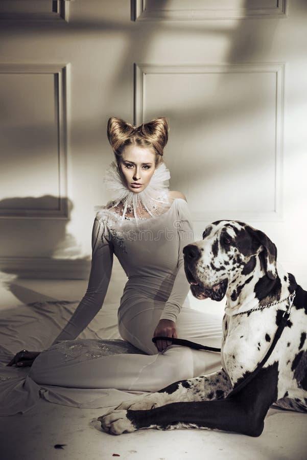 放松与她友好的狗的典雅的小姐 免版税库存图片