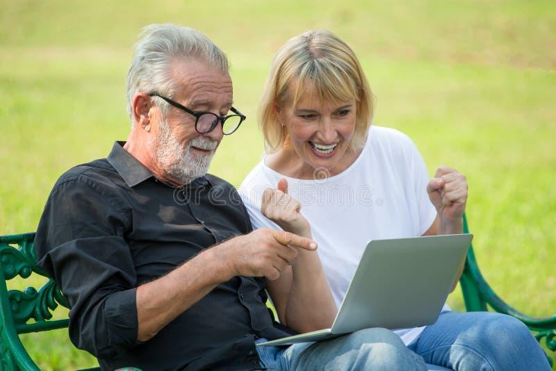 放松与手提电脑的愉快的资深爱恋的夫妇在早晨时间一起激发的公园 老人坐长凳 图库摄影