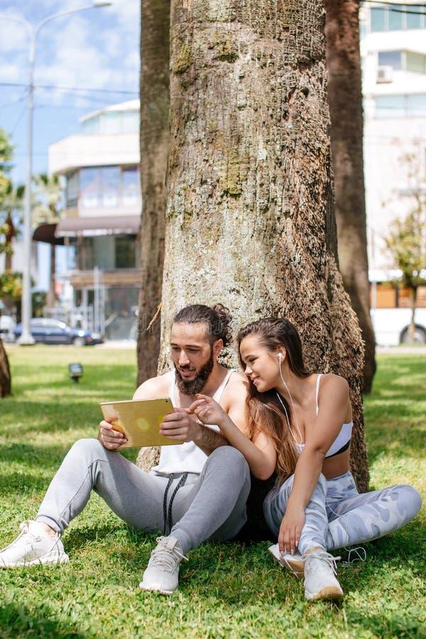 放松与数字式片剂的男人和妇女在公园在体育训练以后 免版税库存图片