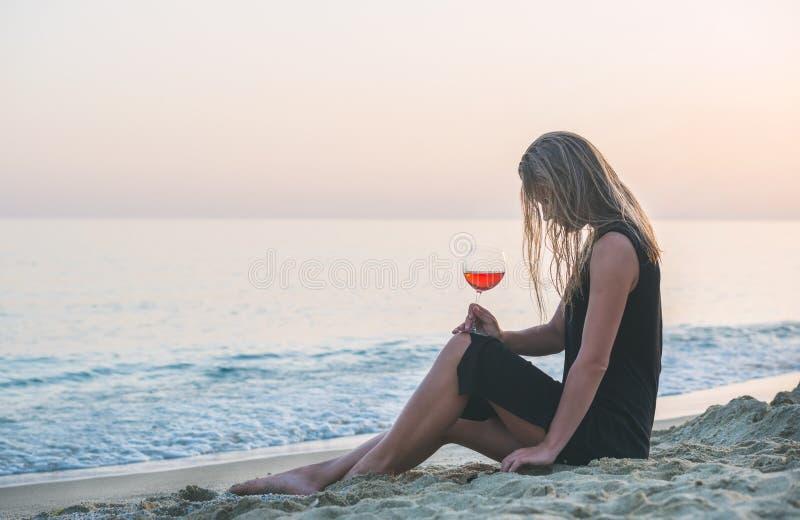 放松与杯的年轻白肤金发的妇女在海滩的玫瑰酒红色由海在日落 免版税库存图片