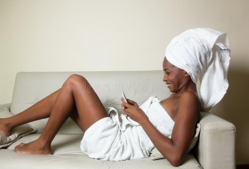 放松与电话的非裔美国人的妇女在浴以后 免版税库存照片