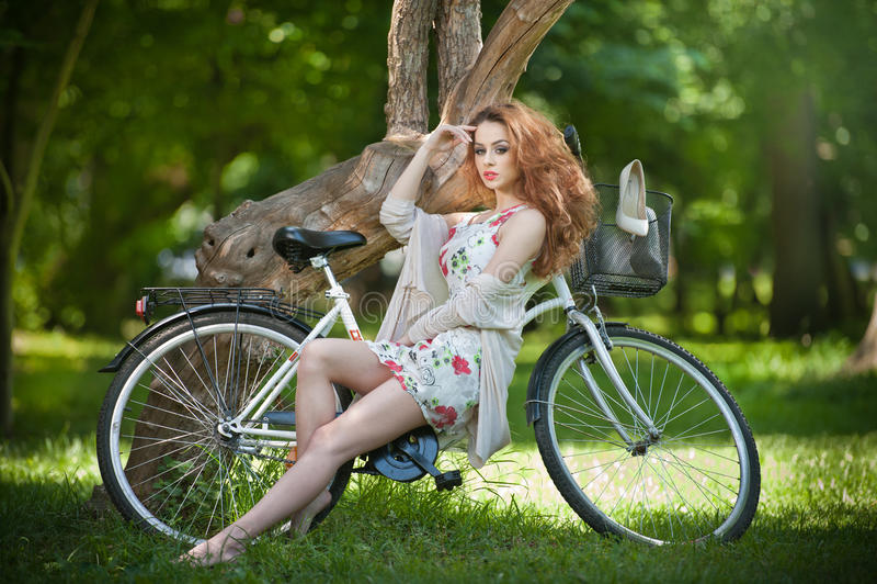 放松与自行车的美丽的红头发人在夏天公园 库存照片