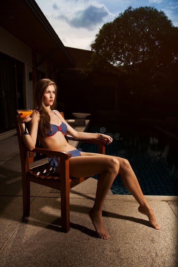 放松与鸡尾酒的比基尼泳装的美丽的妇女 库存图片