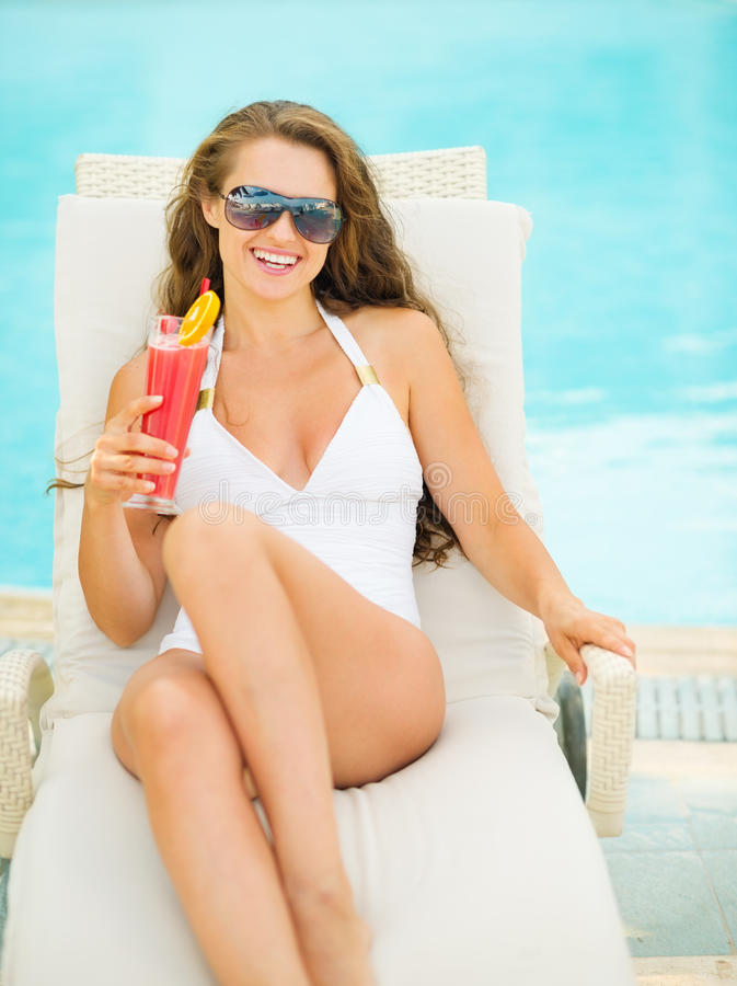 放松与鸡尾酒的泳装的愉快的妇女 库存图片