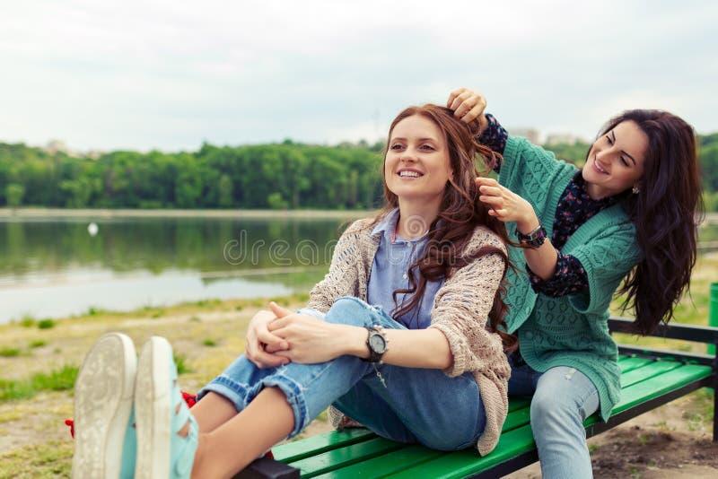 放松两的美女,当做一起时享受时间的发型 免版税库存照片