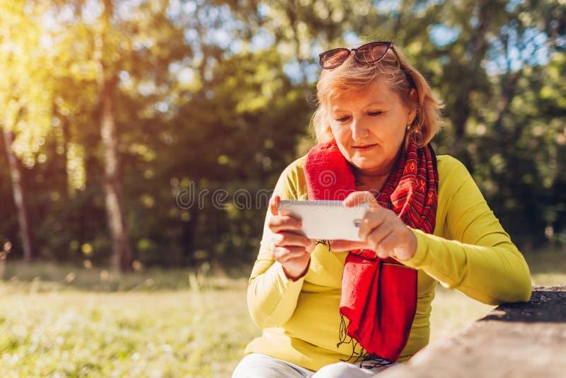 放松使用电话的中年妇女户外 资深在智能手机的夫人观看的录影在秋天森林里 免版税图库摄影