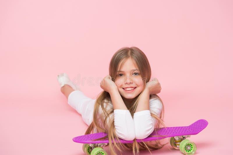 放松和乐趣 愉快的童年 孩子女孩放松精瘦的便士板 现代青年爱好 少女休闲概念 愉快的女孩 免版税库存照片