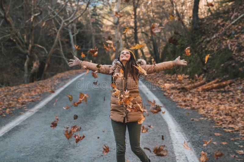 放松和享受秋季的一美丽的年轻女人的画象 免版税库存照片