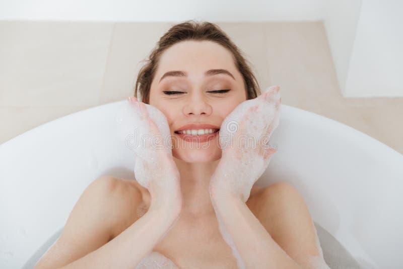 放松和享用与在浴缸的泡沫的快乐的逗人喜爱的妇女 免版税库存照片