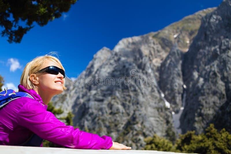 放松和休息在美丽的山的微笑的妇女 库存照片