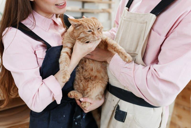 放松和使用与一只大红色猫的美好的夫妇在手上 免版税库存照片