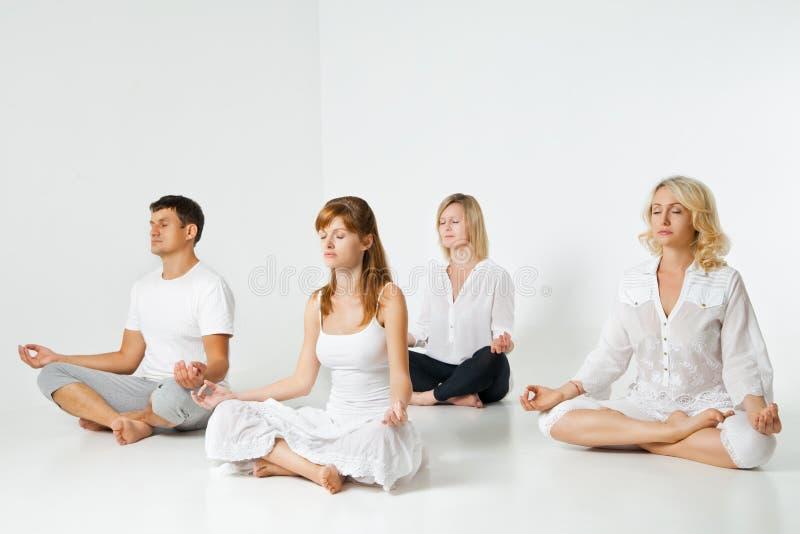 放松和做在白色的人瑜伽 免版税库存图片
