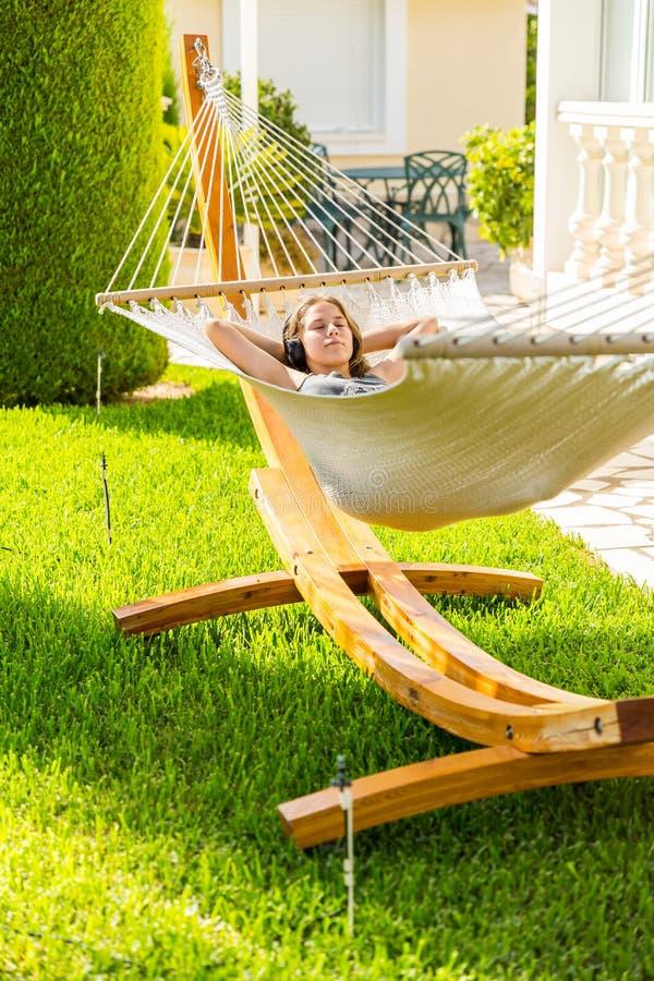 放松和听到在吊床的音乐的女孩 免版税库存图片