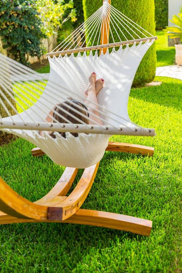 放松和听到在吊床的音乐的女孩 图库摄影