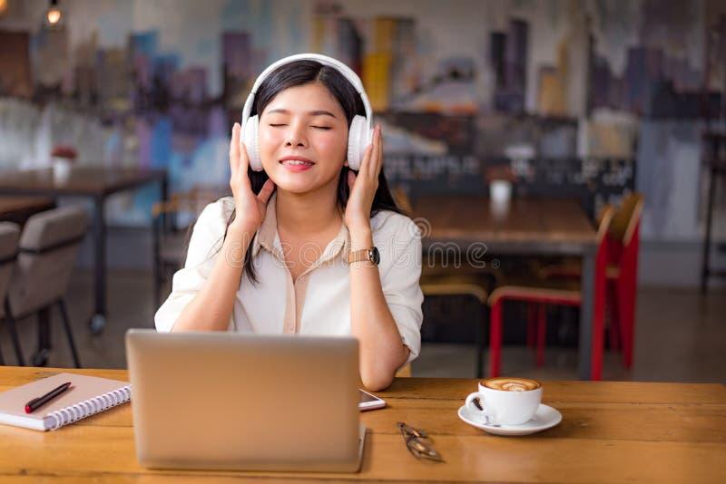 放松和听到在咖啡馆wi的音乐的美丽的亚裔妇女 库存图片