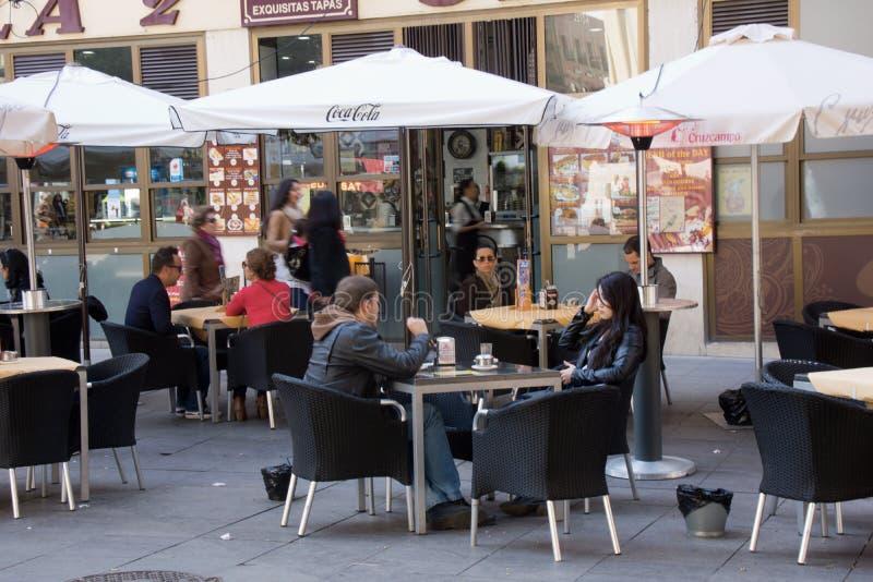 放松和喝在大阳台的人们 免版税库存照片
