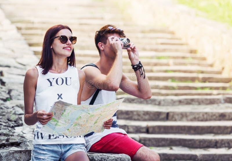 放松和审查指南地图的两个年轻游人 免版税库存图片