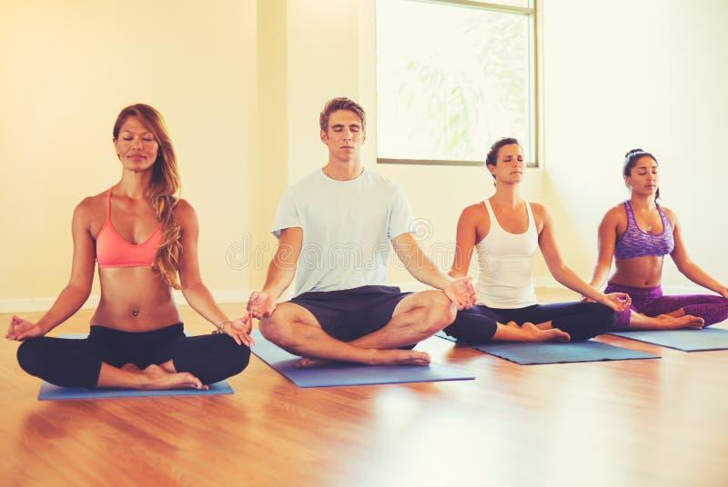 放松和思考在瑜伽类的人们 图库摄影