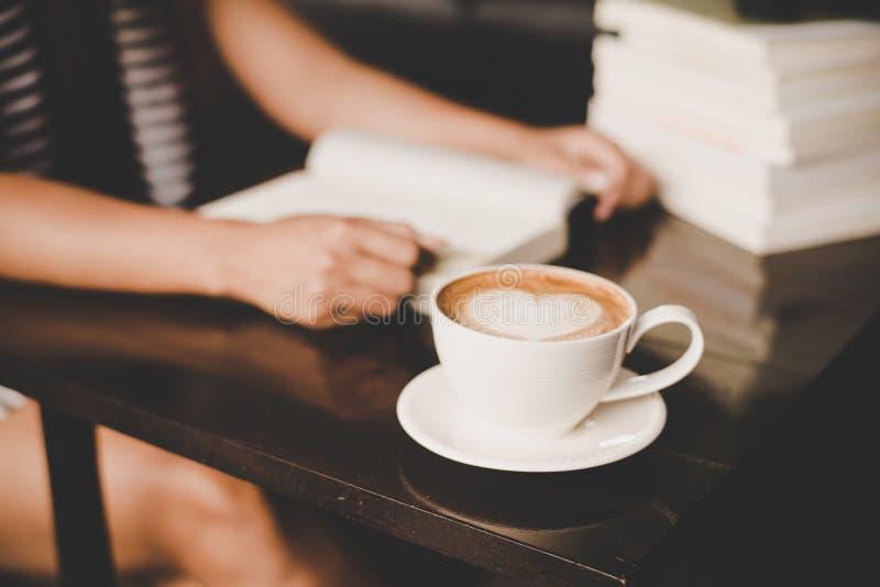 放松和读在咖啡馆的亚裔妇女一本书 妇女lifes 库存图片