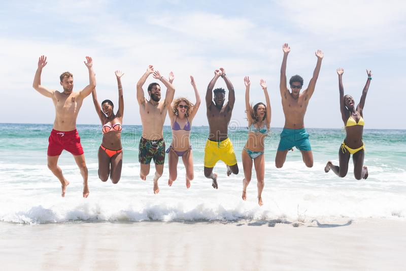 放松和跳跃在水中的小组朋友在海滩 免版税库存照片