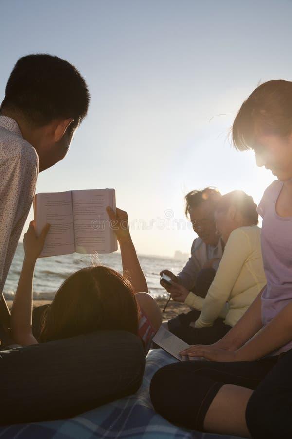 放松和读在海滩的多代家庭 免版税库存照片