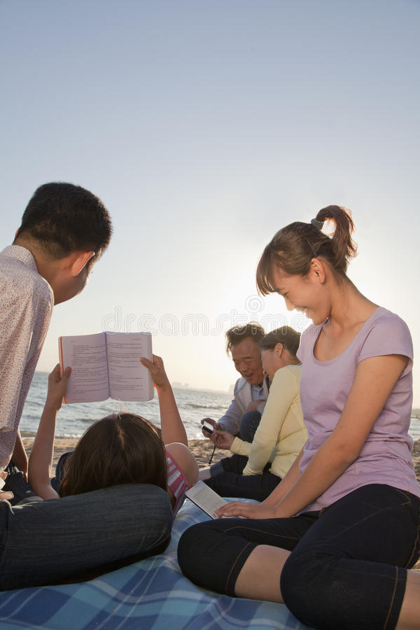 放松和读在海滩的多代家庭 库存图片